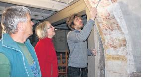 Restaurator Simon Gebler (rechts) erklärt Pastorin Else Bernds-Fischer und Thomas Herold, welche Stellen der mittelalterlichen Malerei er noch ausbessern möchte. FOTO: JANA OTTO